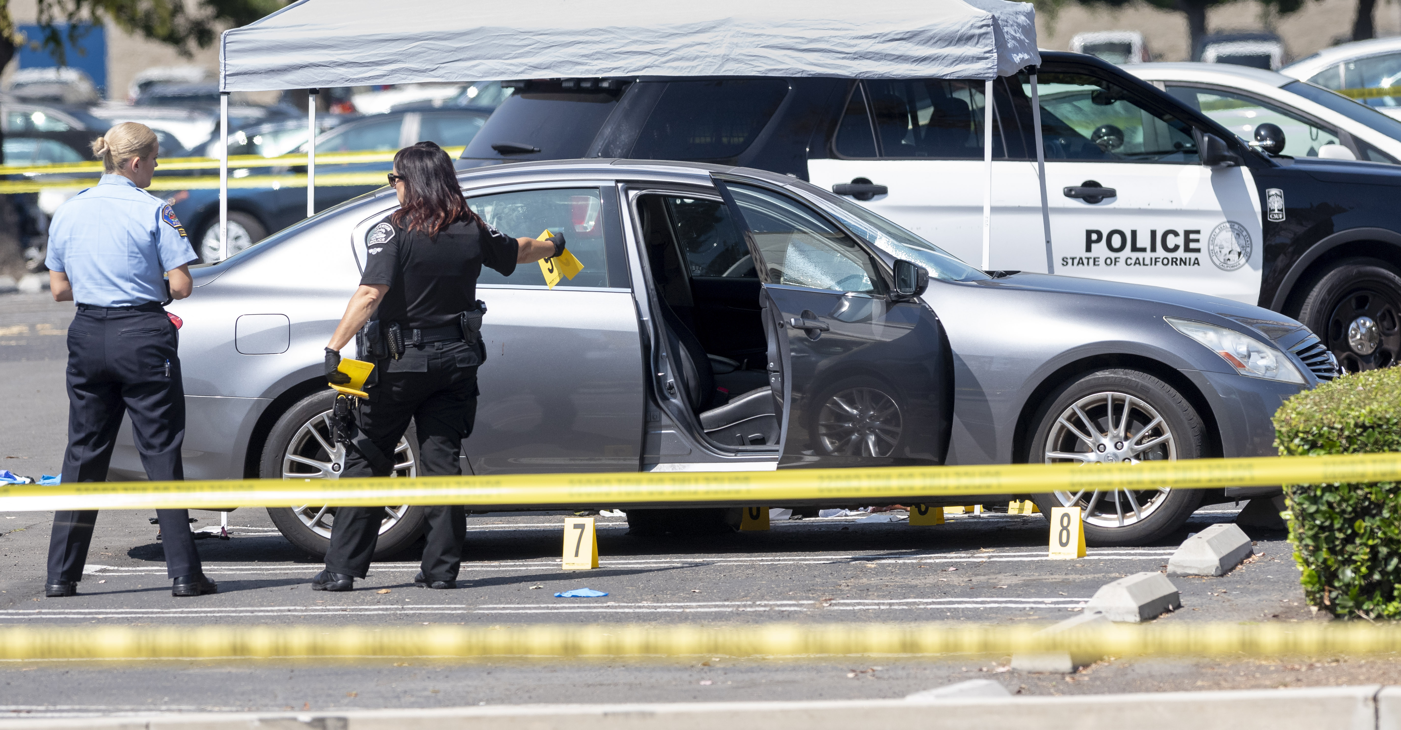 Police investigate a car where a retired Cal State Fullerton administrator was stabbed to death in Fullerton, Calif. on Aug. 19, 2019.