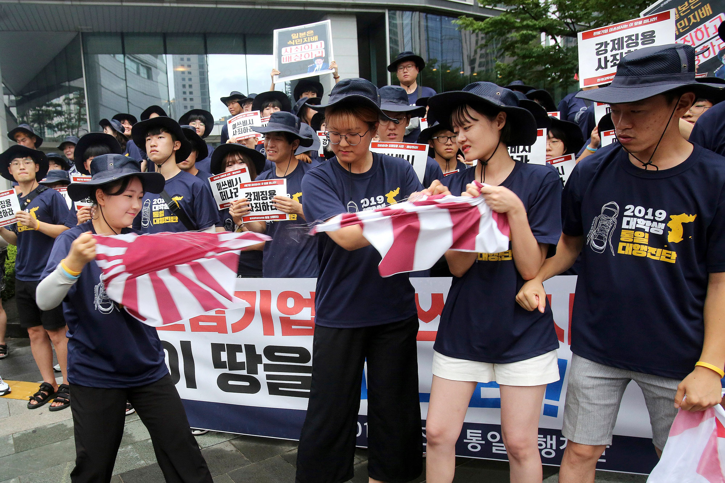 South Korean college students tear a banner showing an image of a Japanese rising sun flag during a rally to denounce Japan's new trade restrictions on South Korea in front of the office of Mitsubishi Corp. in Seoul, South Korea, on Aug. 7.