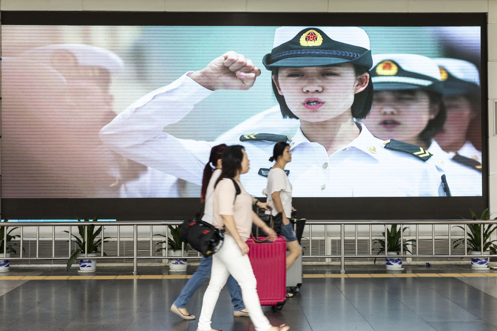 Travelers walk past an advertisement for the People's Liberation Army (PLA) on a screen near the Luohu border crossing in Shenzhen, China, on Aug. 4, 2019.