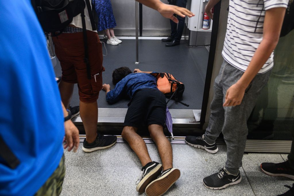 A man (C) falls down during a protest to prevent commuters from reaching work in business districts at Lai King MTR station in Hong Kong on August 5, 2019.