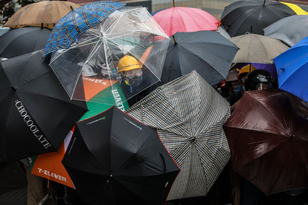 Protesters shield themselves with umbrellas against pepper spray used by the police during a rally in Hong Kong on June 12, 2019.