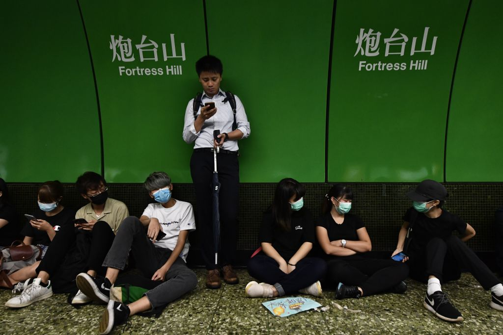 Protesters sit on a platform of a MTR underground train after some blocked the train doors at Fortress Hill station in Hong Kong on Aug. 5, 2019.
