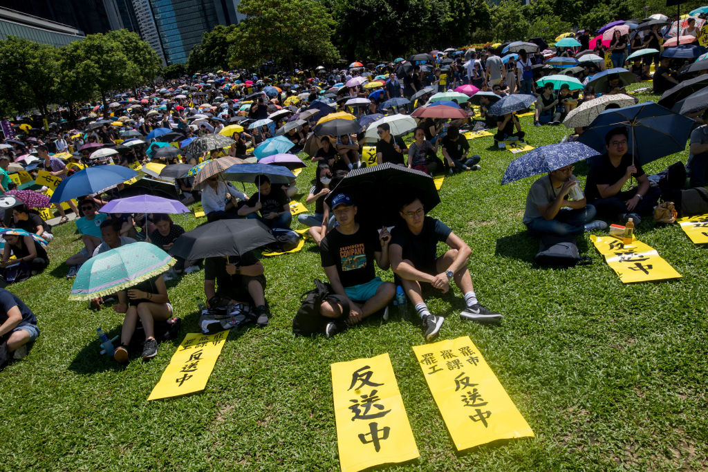 Demonstrators take shelter under their umbrellas as they sit on the ground at Tamar Park outside the Chief Executive's Office in Hong Kong on Aug. 5, 2019.
