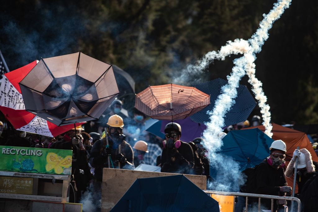 Protesters stand amid tear gas fired by the police in Tai Po district during a general strike in Hong Kong on Aug, 5, 2019.