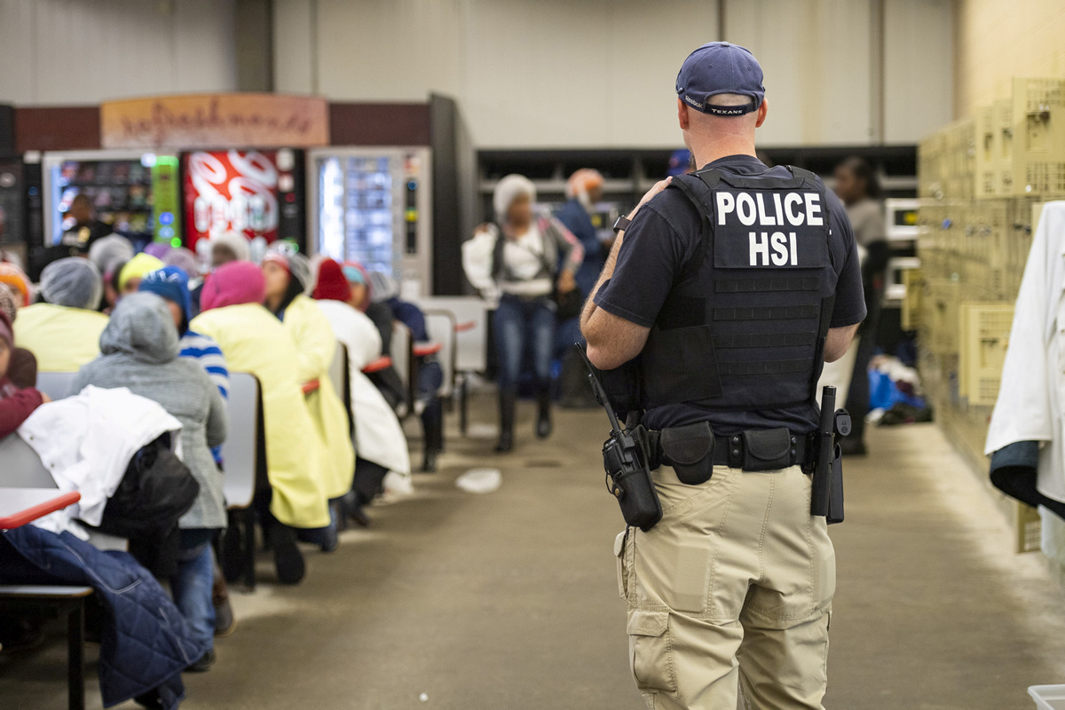 Homeland Security Investigations officers from Immigration and Customs Enforcement (ICE) look on after executing search warrants and making arrests at an agricultural processing facility in Canton, Mississippi, on Aug. 7, 2019.