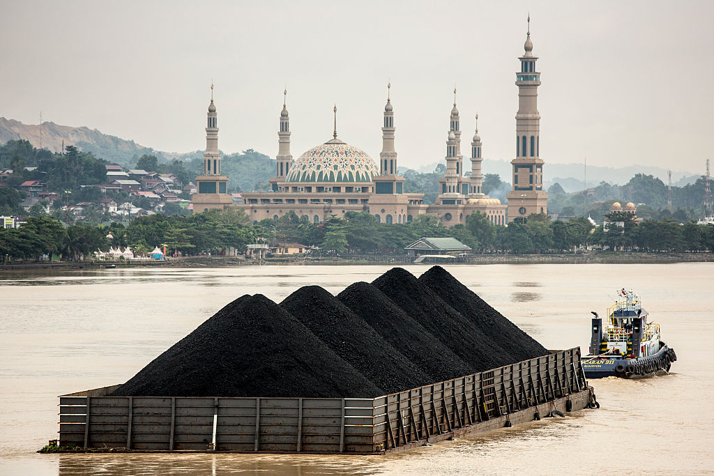 A tug pulls a coal barge past the Islamic centre in Samarinda, Kalimantan, Indonesia on Aug. 26, 2016.