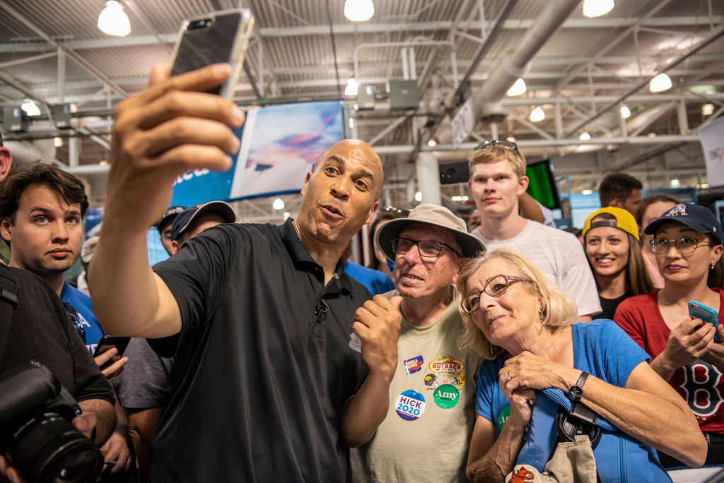 Democratic presidential candidate U.S. Sen. Cory Booker (D-NJ) records a video with a couple for their son at the Iowa State Fair on August 10, 2019 in Des Moines, Iowa.