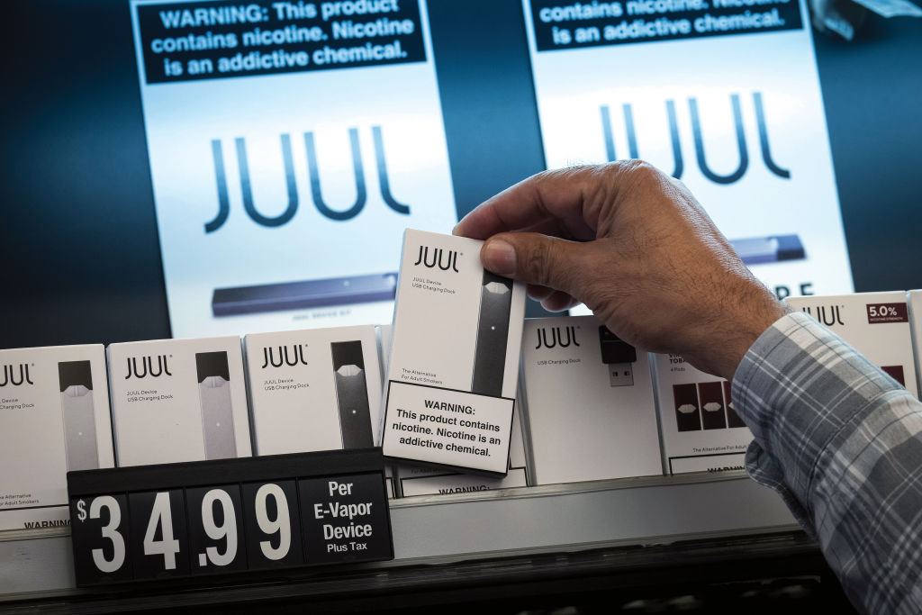 An employee picks up a Juul Labs Inc. device kit for a customer at a store in San Francisco, California, on June 26, 2019.