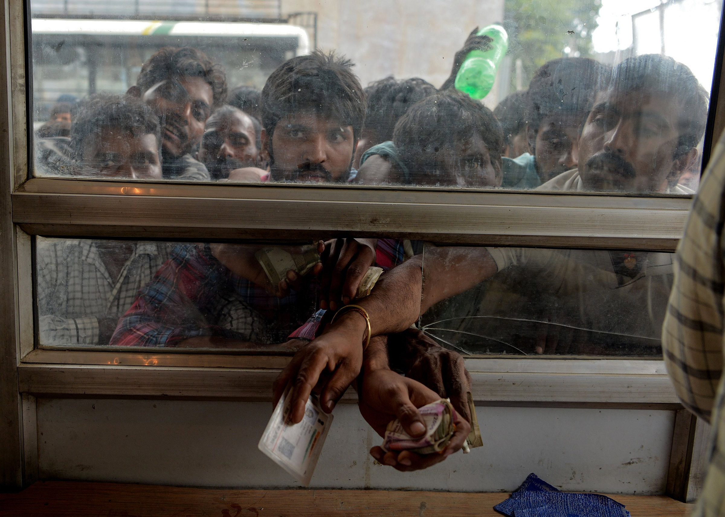 Laborers buy bus tickets at a counter of Jammu and Kashmir Tourist Reception Centre (JKTRC) in Srinagar on Aug. 7