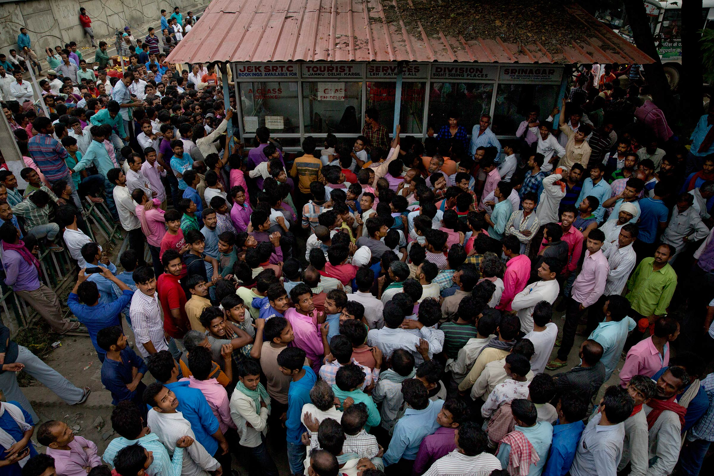 Indian migrant workers crowd outside the government transport yard to buy bus tickets to leave the region, during curfew in Srinagar, Indian controlled Kashmir, Wednesday, Aug. 7.