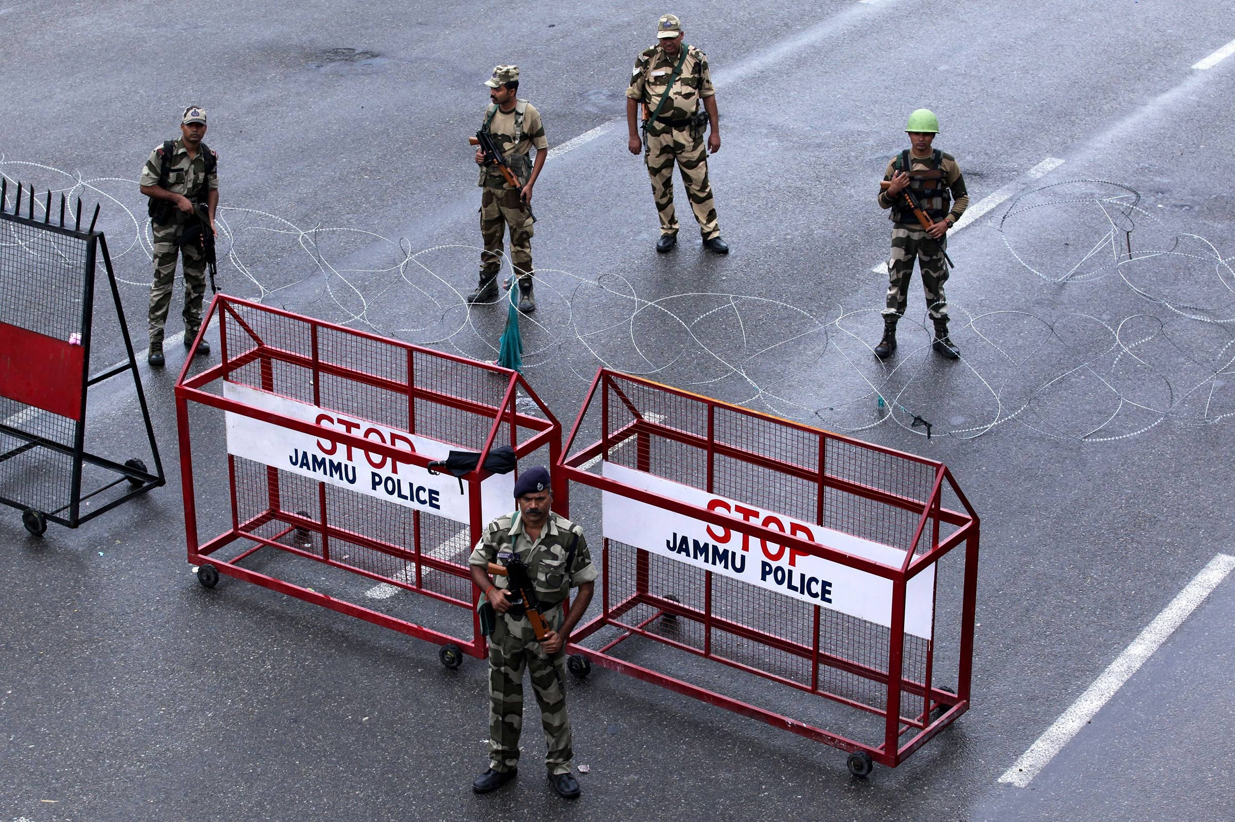 Security personnel stand guard at a roadblock in Jammu on August 7. A protester died after being chased by police during a curfew in Kashmir's main city, left in turmoil by an Indian government move to tighten control over the restive region, a police official said on August 7.