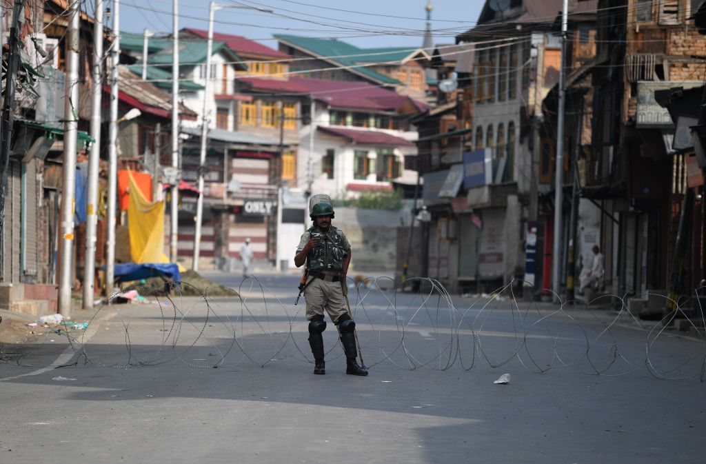 A security personnel stands guard on a street during a curfew in Srinagar on August 6, 2019.