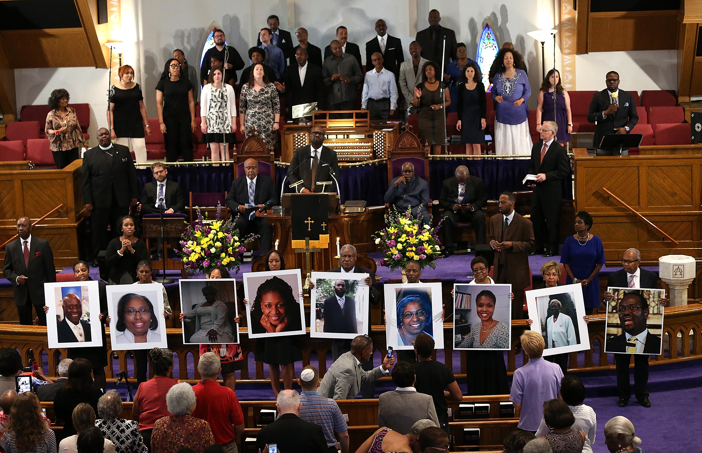 Photographs of the nine victims killed at the Emanuel African Methodist Episcopal Church in Charleston are held up by congregants during a prayer vigil at the the Metropolitan AME Church June 19, 2015 in Washington, DC.