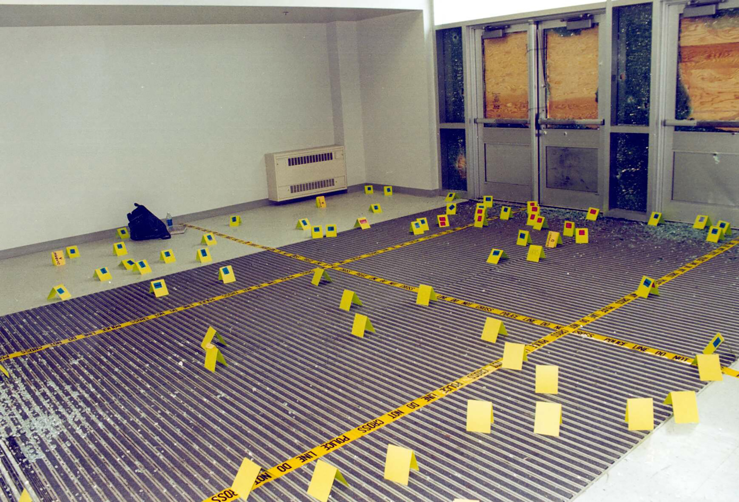 View of damage to the west entryway to Columbine High School where teenage gunmen Eric Harris and Dylan Klebold entered the school April 20, 1999 in Littleton, Colo. Flags mark points where evidence such as bullet casings were found.