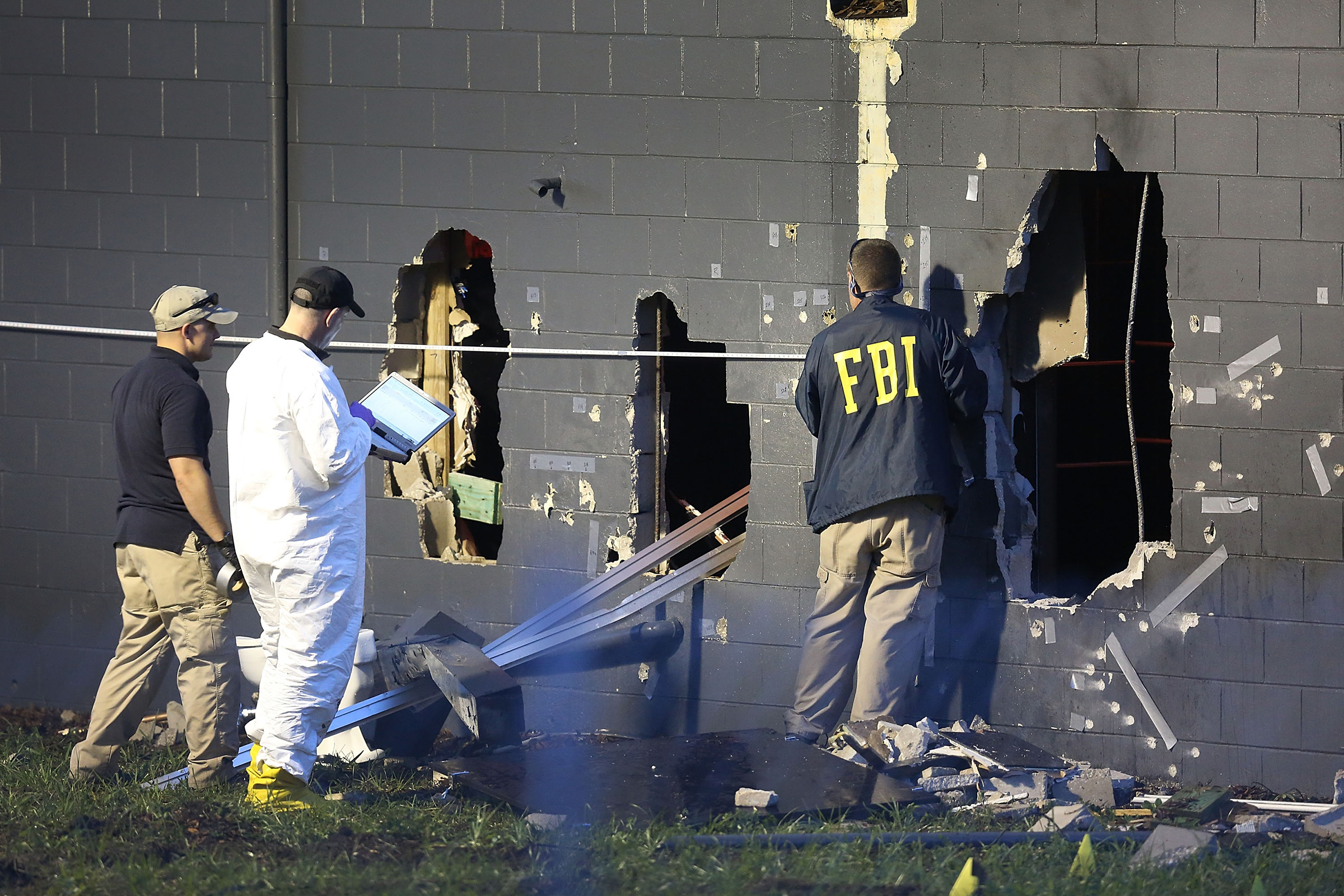 FBI agents investigate near the damaged rear wall of the Pulse Nightclub where Omar Mateen allegedly killed at least 50 people on June 12, 2016 in Orlando.