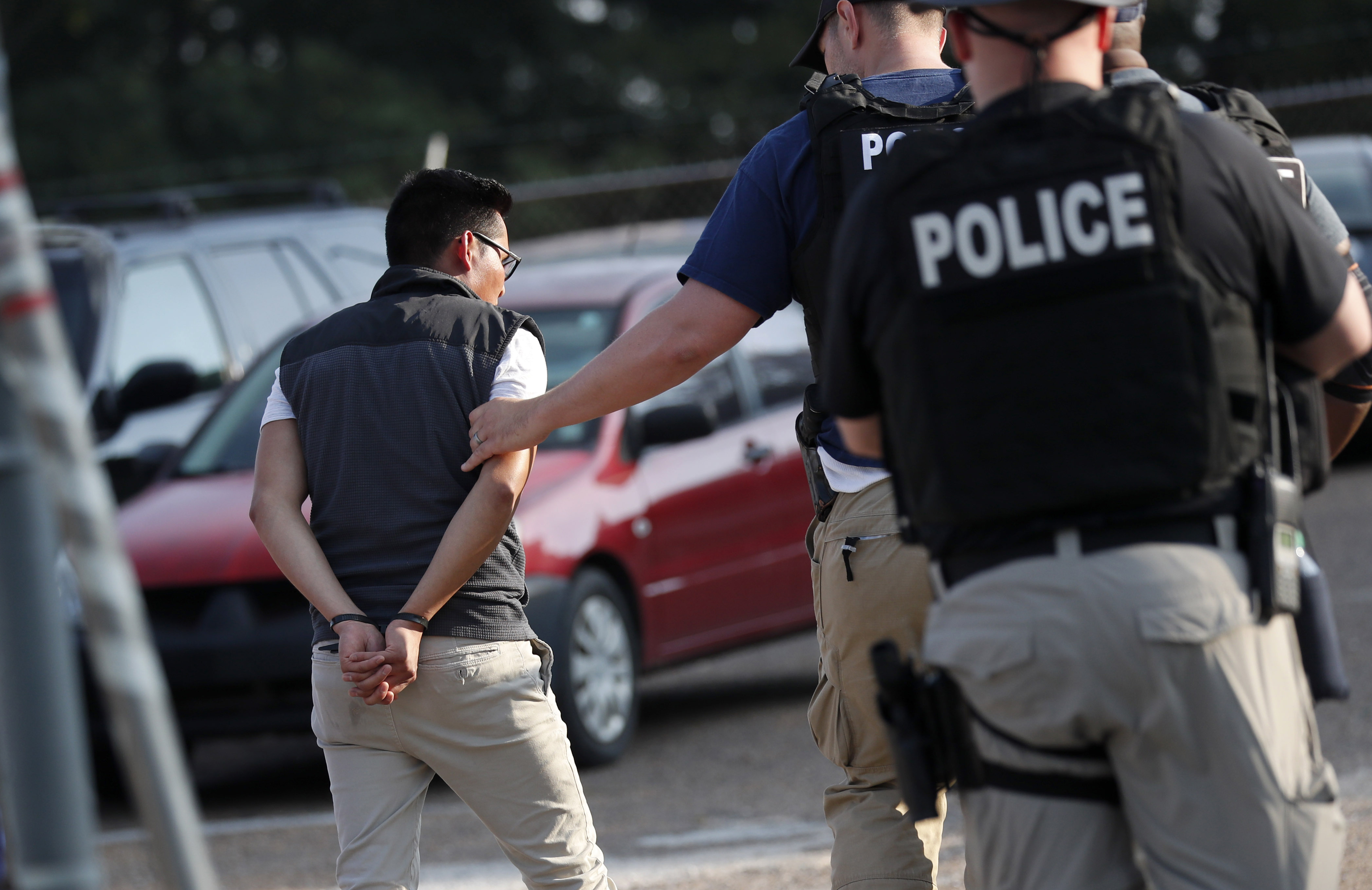 A man is taken into custody at a Koch Foods Inc. plant in Morton, Miss., on August 7, 2019.