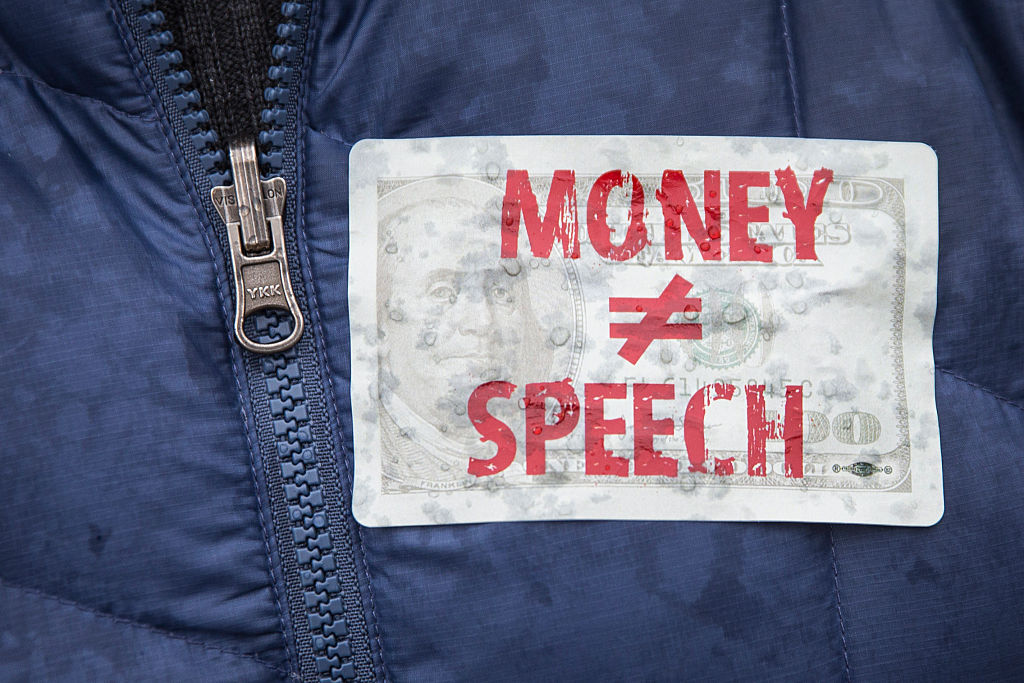 In this file photo, an attendee wears a sticker against money in politics during a rally calling for an end to corporate money in politics and to mark the fifth anniversary of the Supreme Court's Citizens United decision, at Lafayette Square near the White House, January 21, 2015 in Washington, DC.