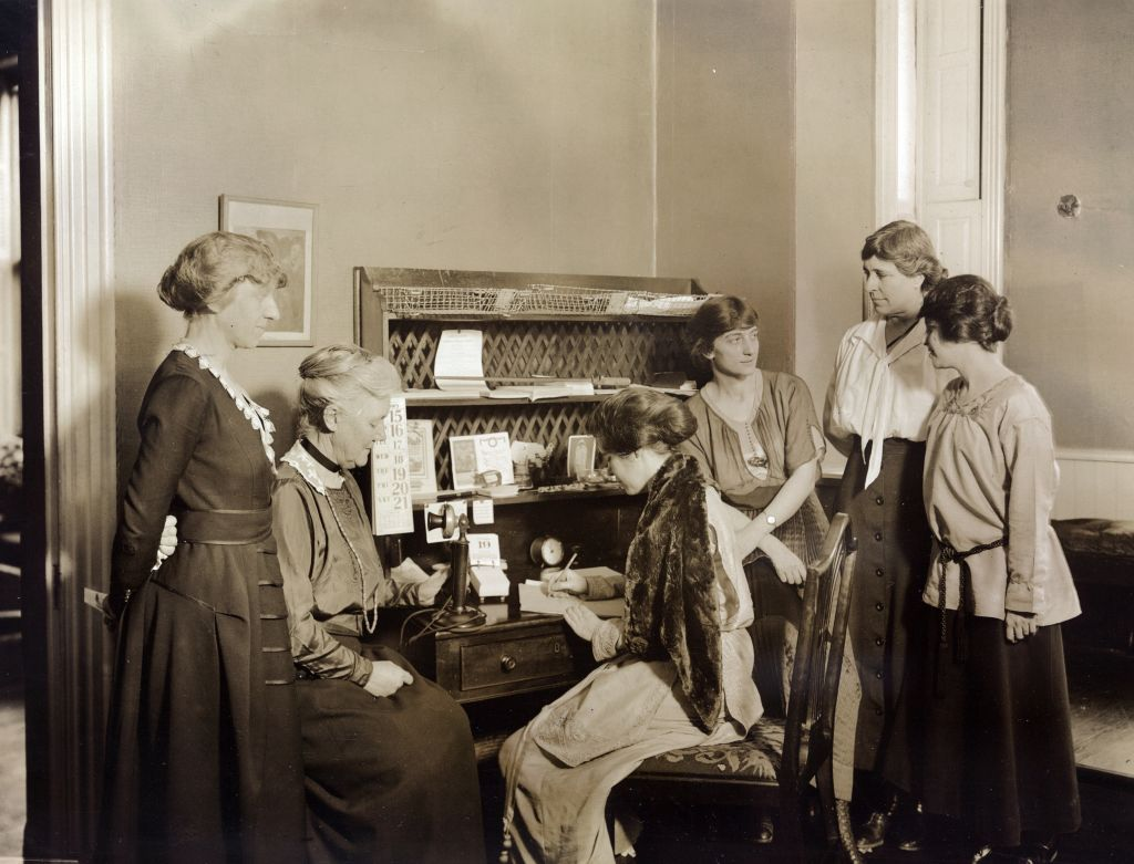 Six National Woman's Party members gathered around a desk at National Woman's Party headquarters. Left to right: Mabel Vernon, Dora Lewis, Alice Paul (seated), Florence Brewer Boeckel, Abby Scott Baker, and Anita Pollitzer. Feb. 1921.