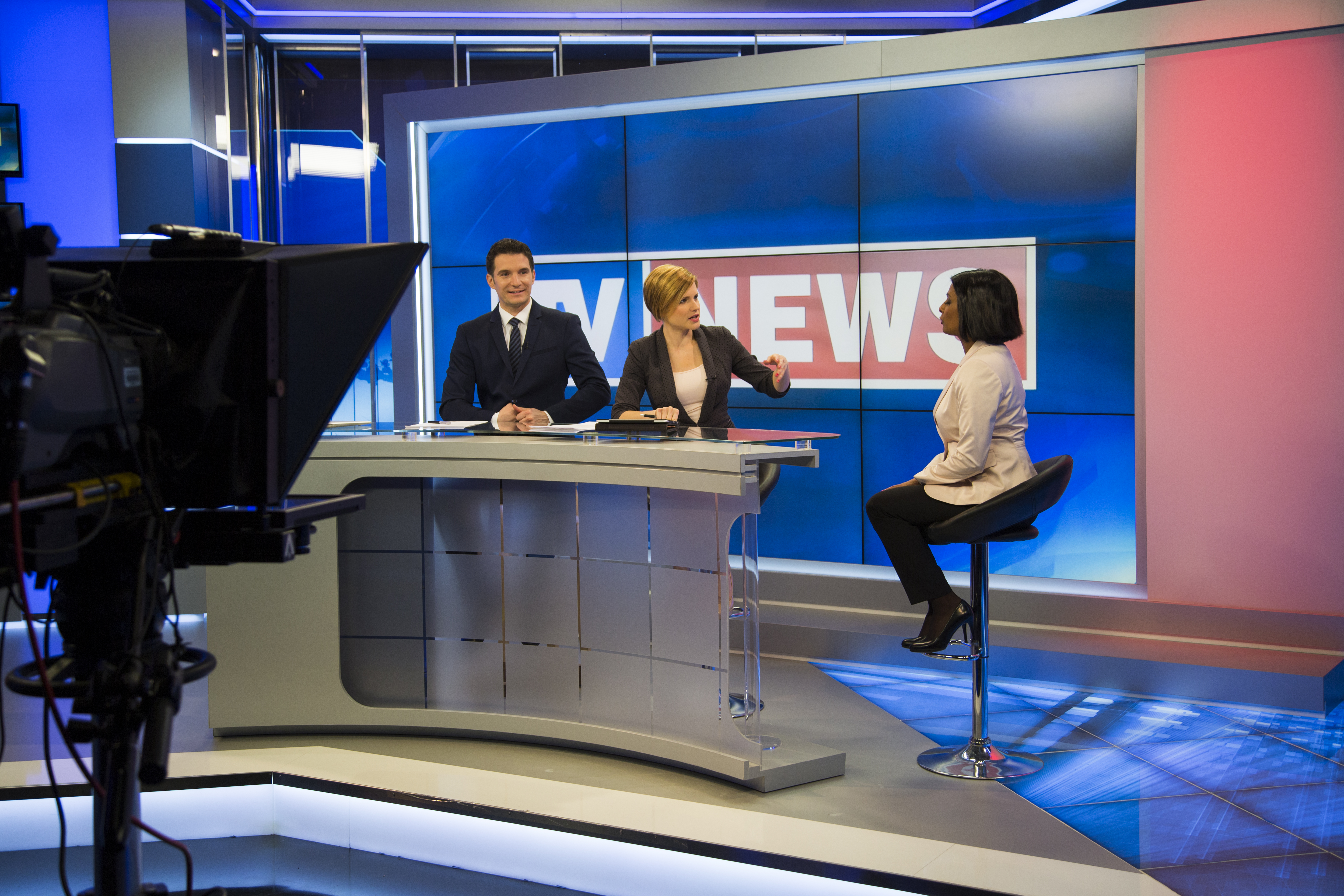 Two commentators preparing for a live interview on the news. Three people in a tv studio talking about the script for the news show.
