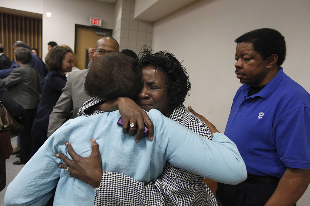 Shirley Burns, center, hugs her friend after a judge found that racial bias played a role in the trial and death row sentencing of Burns' son Marcus Robinson on Friday, April 20, 2012, in Fayetteville, North Carolina. The ruling meant Robinson's sentence was immediately converted to life without possibility for parole.