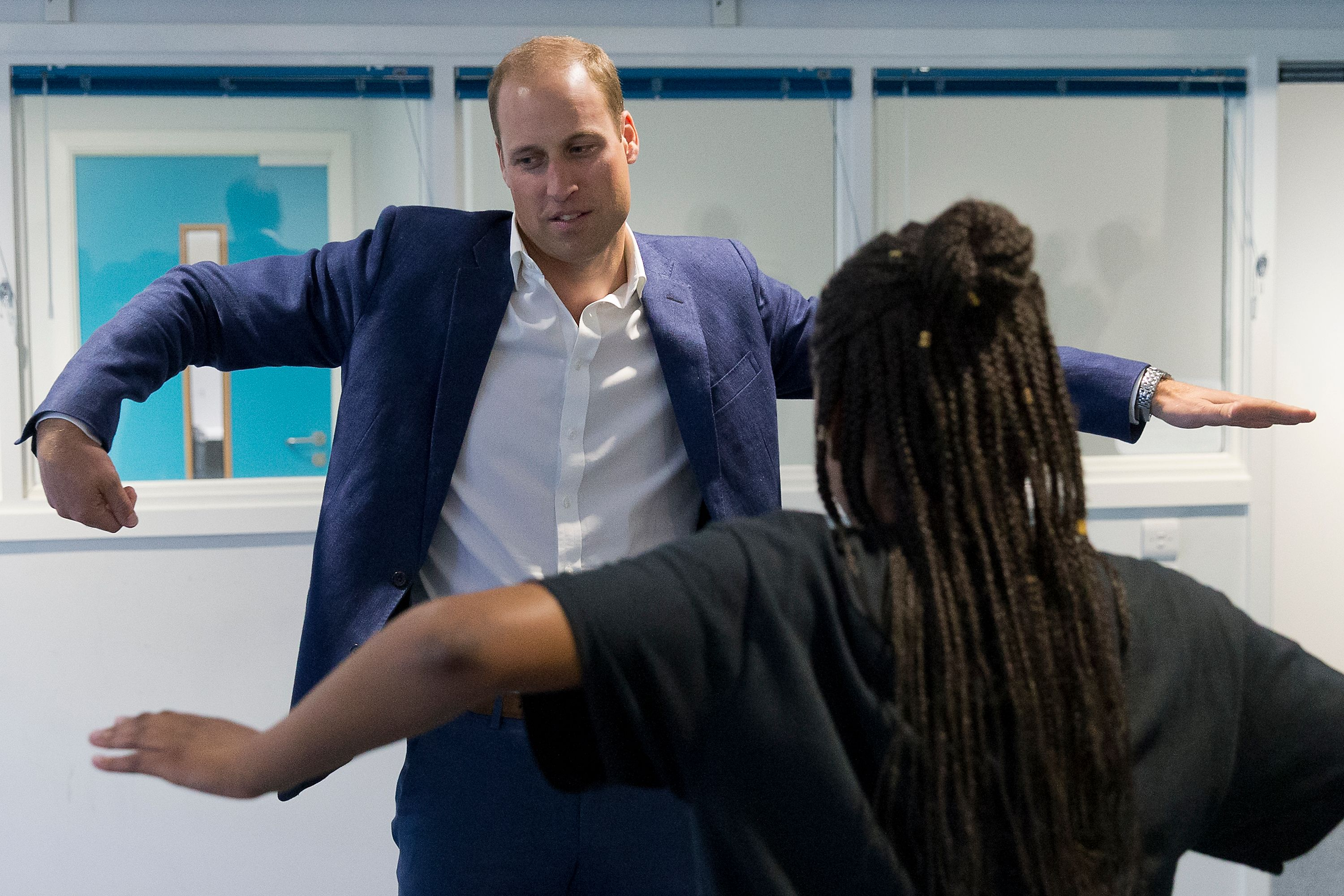 Britain's Prince William, Duke of Cambridge, learns a dance move with Scariofunk dance collective during a visit to Caius House Youth Centre in London on September 14, 2016. -