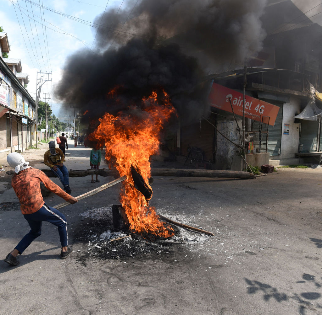 A protester holds a burning tire near a barricade set by the local protesters to block the road during a protest against the abolishing of Article 370, on August 20, 2019 on the outskirts of Srinagar, India.