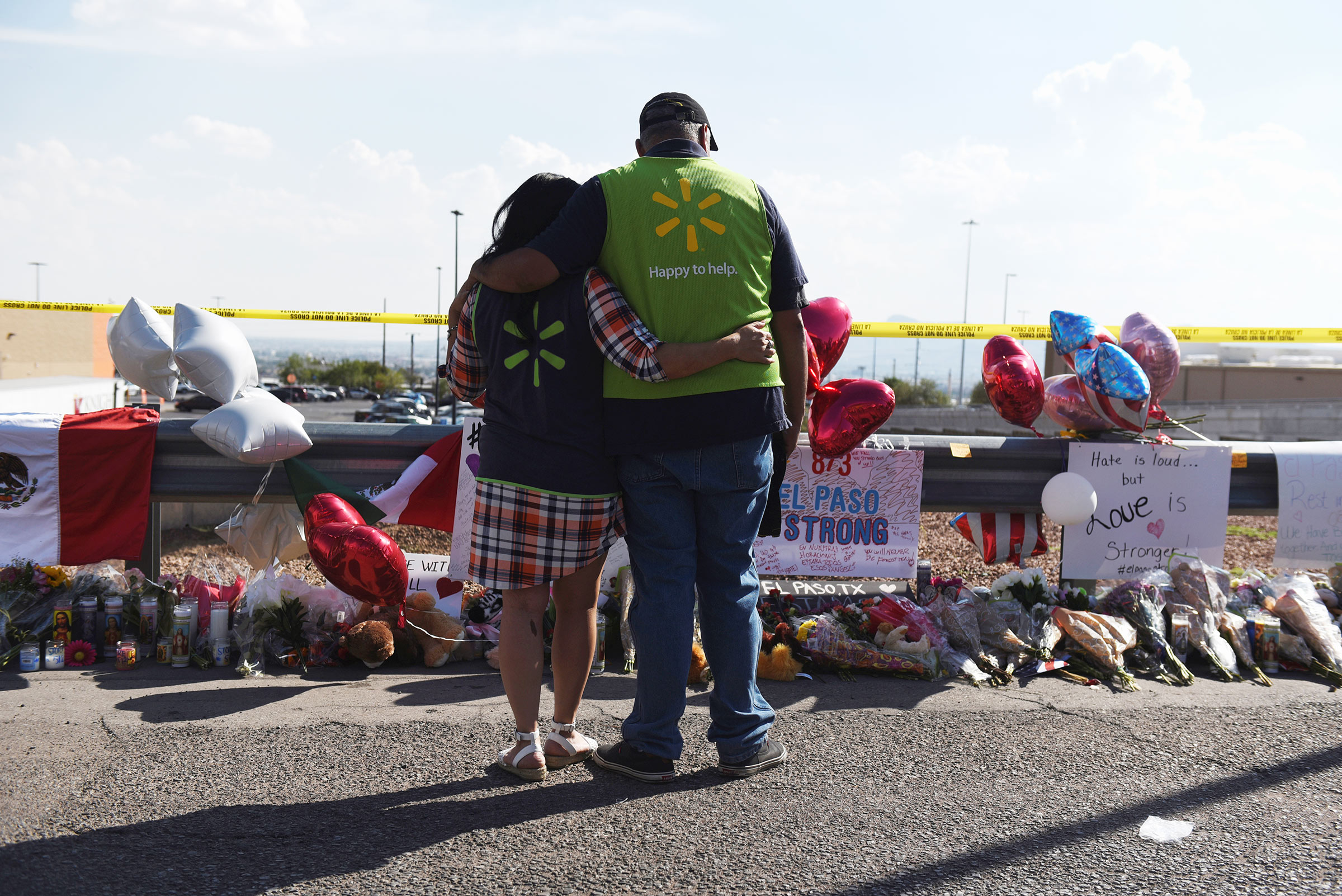 Walmart employees pay their respects at a memorial outside the site of the El Paso mass shooting.