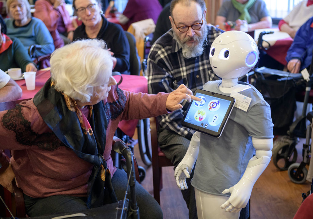 An elderly resident looks to a robot called  Pepper  during a presentation of two robots at the August-Stunz-Altenzentrum senior care facility on November 28, 2018 in Frankfurt, Germany.