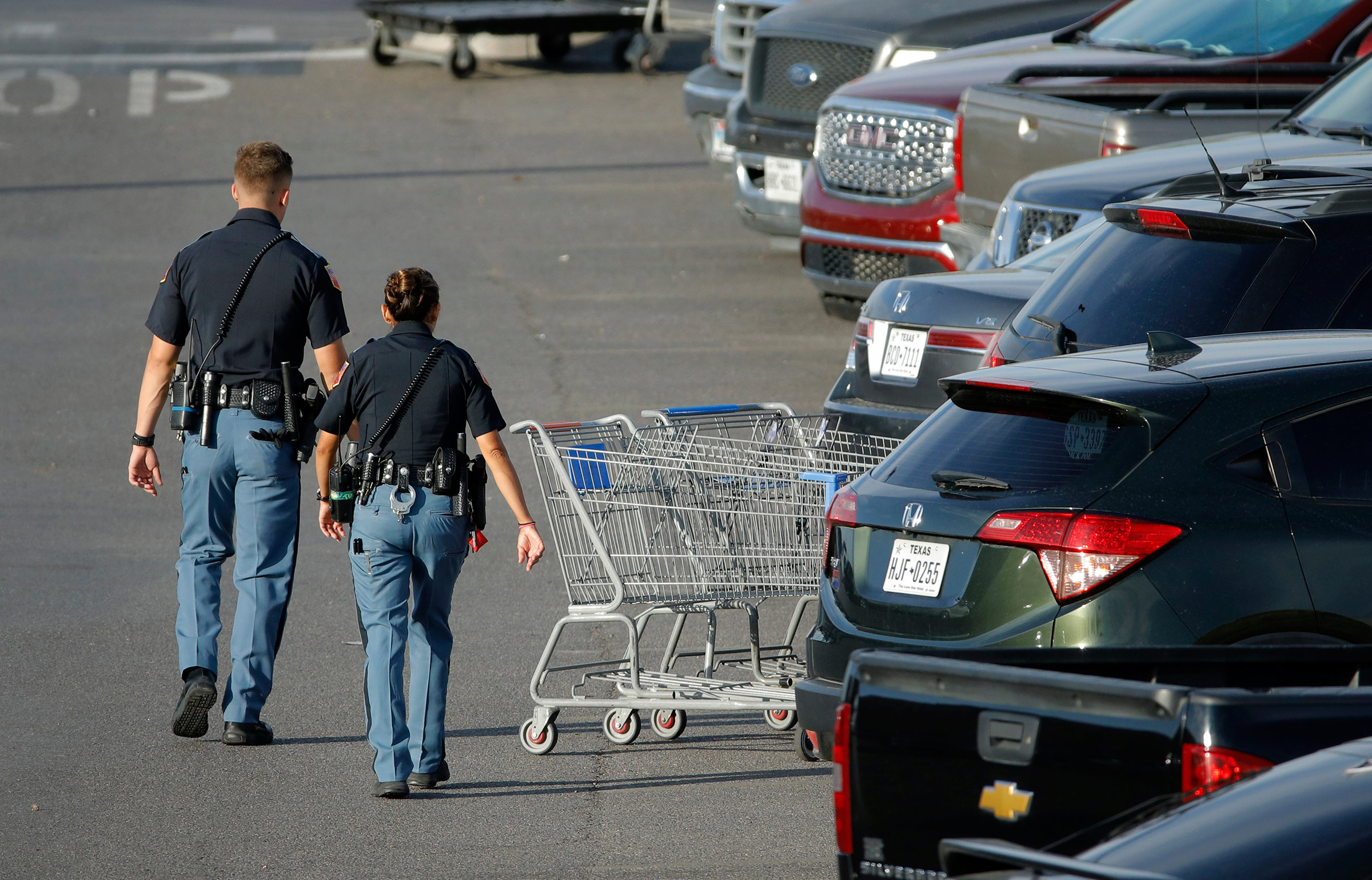 Police officers walk by shopping carts at the scene of the El Paso mass shooting, on Aug. 4