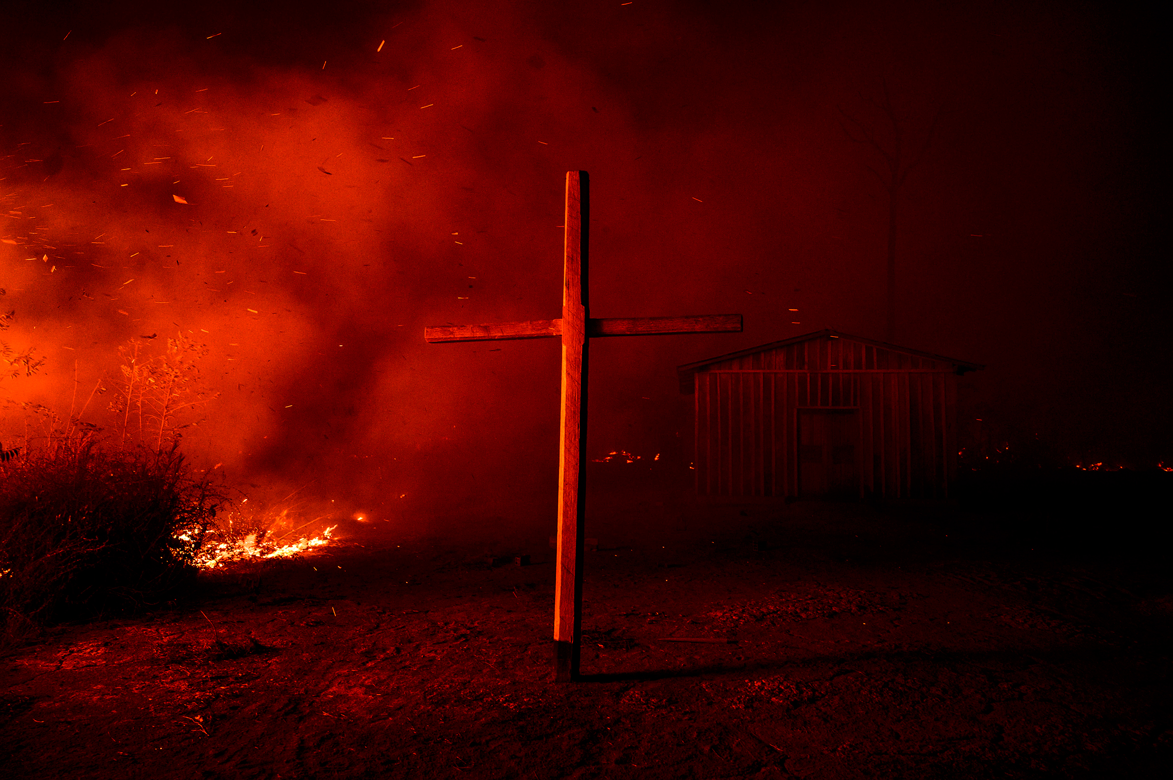 A church is enveloped in smoke from nearby flames in the region of Vila Nova Samuel on Aug. 27.