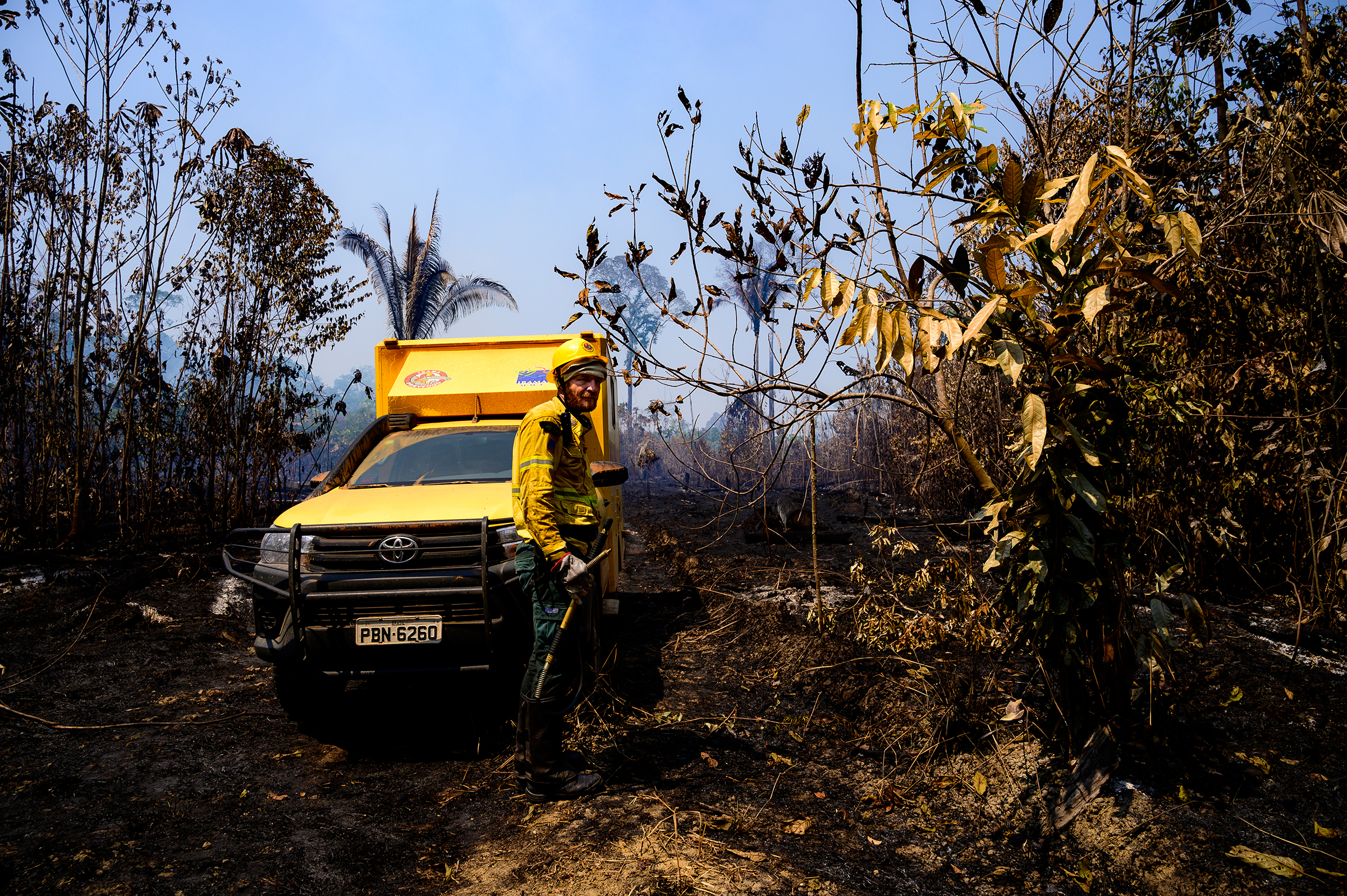 A worker and vehicle from Brazil's environmental agency, IBAMA, in a recently burned section of forest in the Vila Nova Samuel region on Aug. 28.