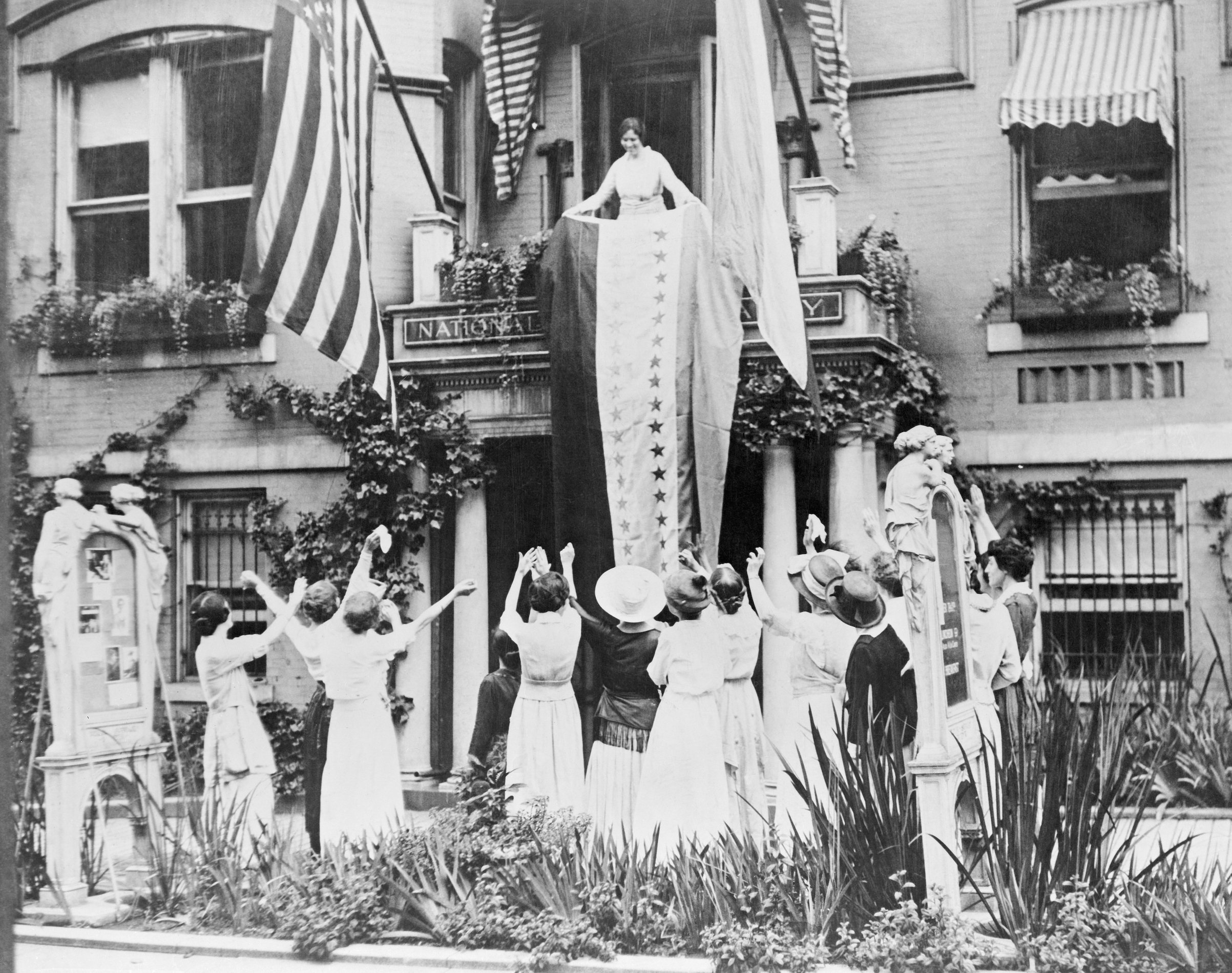 Alice Paul unfurls a banner from the balcony of the National Women's Party headquarters, celebrating the ratification of the 19 Amendment by Tennessee.