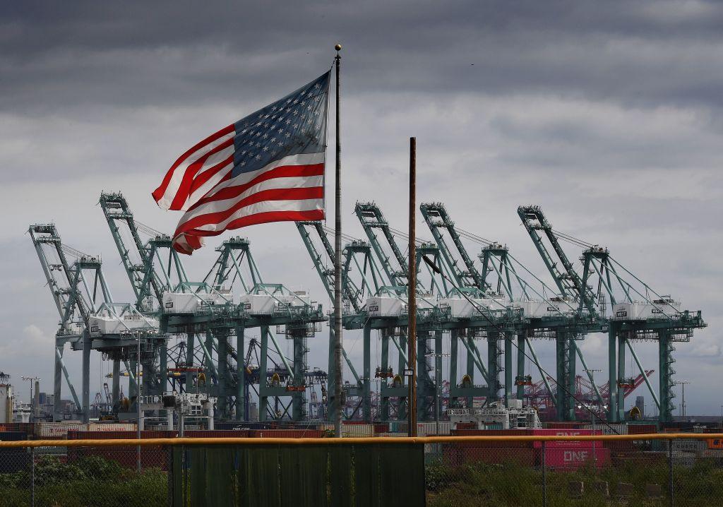 The U.S. flag flies over shipping containers in Long Beach, California on March 4, 2019.