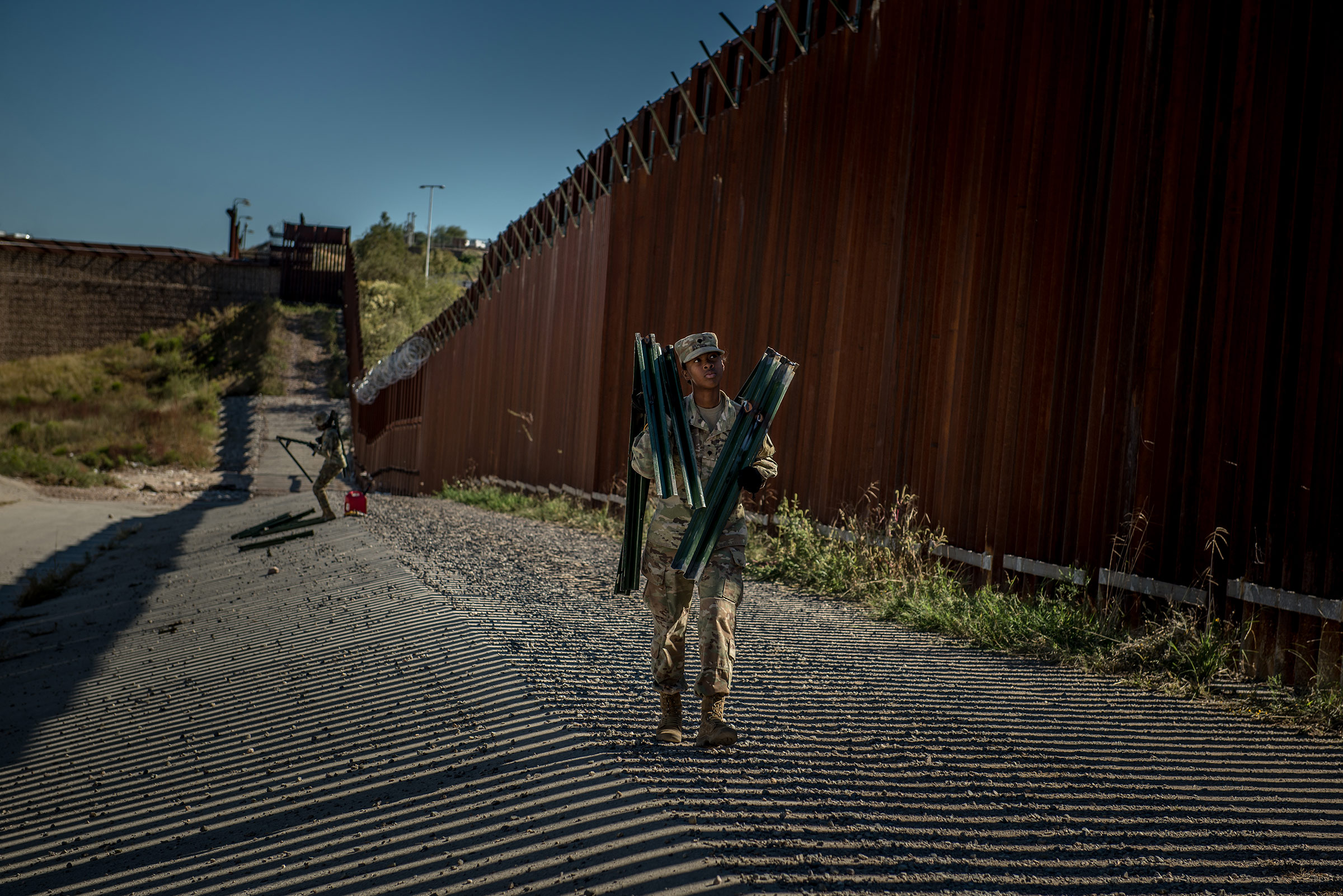 Soldiers install brackets and wire along the border wall in November.