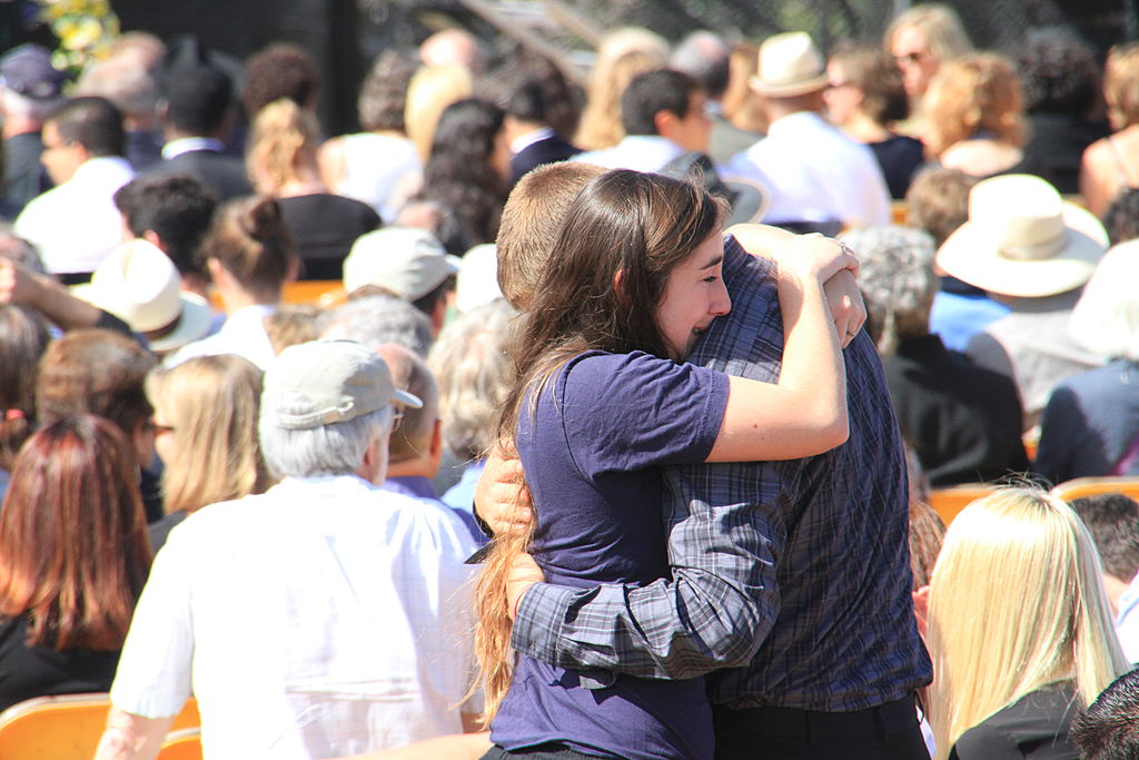 A couple comfort one another before the start of a memorial service at UC Santa Barbara's Harder Stadium to honor six UCSB students slain in a rampage in Isla Vista, California.