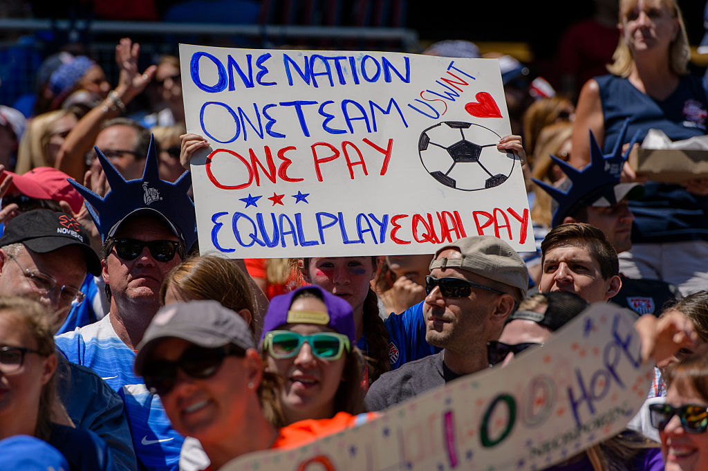 A fan holds and equal play equal pay sign during an international friendly soccer match between South Africa and USA at Soldier Field in Chicago, IL.