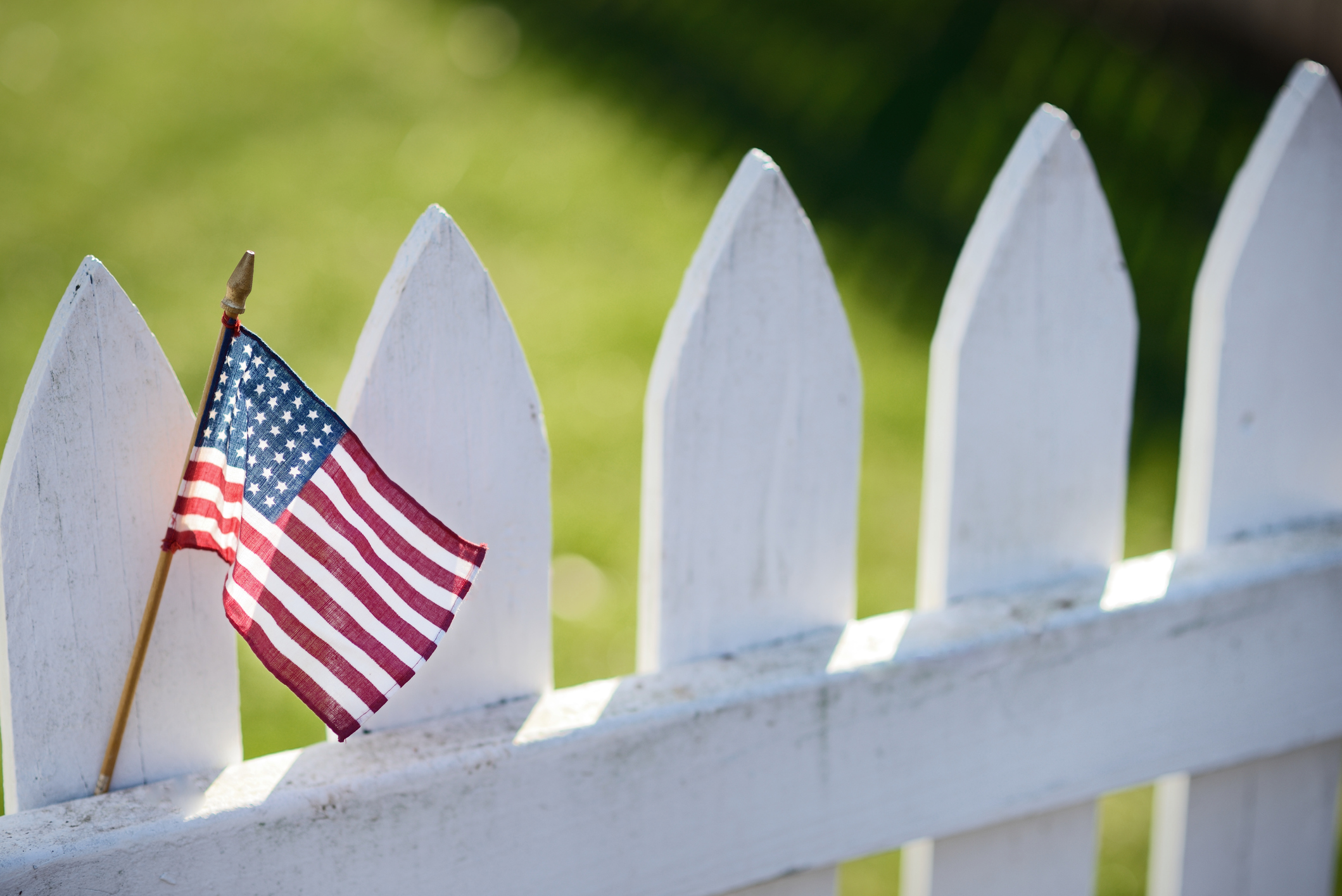 American Flag on white picket fence for Memorial Day or Labor Day.