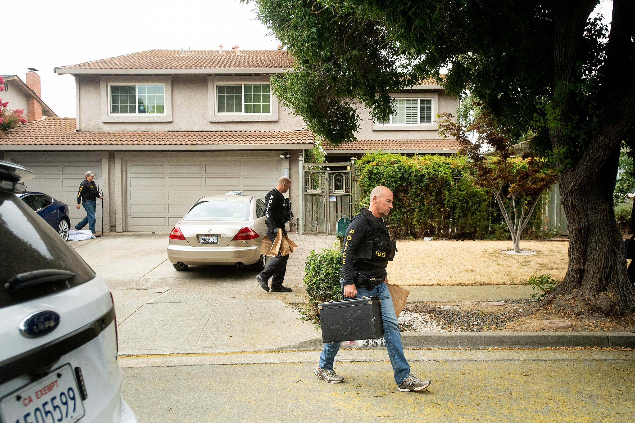 Police carry evidence bags from the home of the Gilroy shooting suspect.