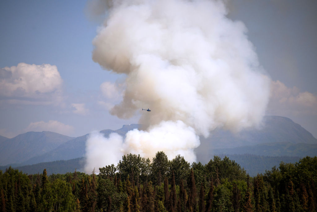 A helicopter passes by as smoke rises from a wildfire on July 3, 2019 south of Talkeetna, Alaska near the George Parks Highway.