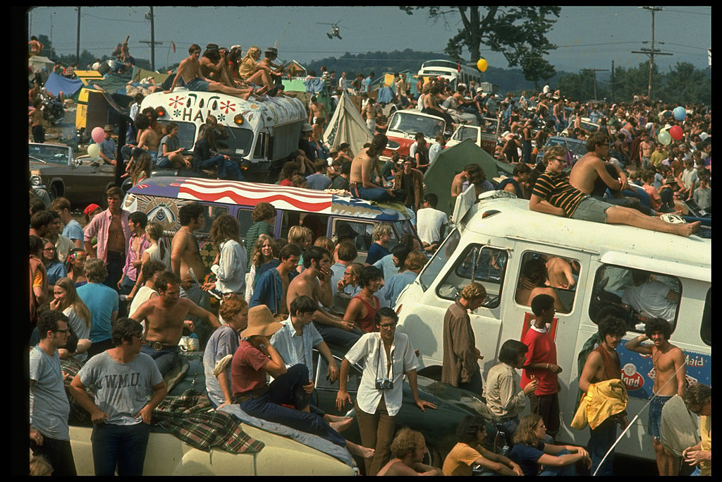 Large crowd of people, including people sitting on top of cars & buses, during the Woodstock Music & Art Fair in August of 1969.
