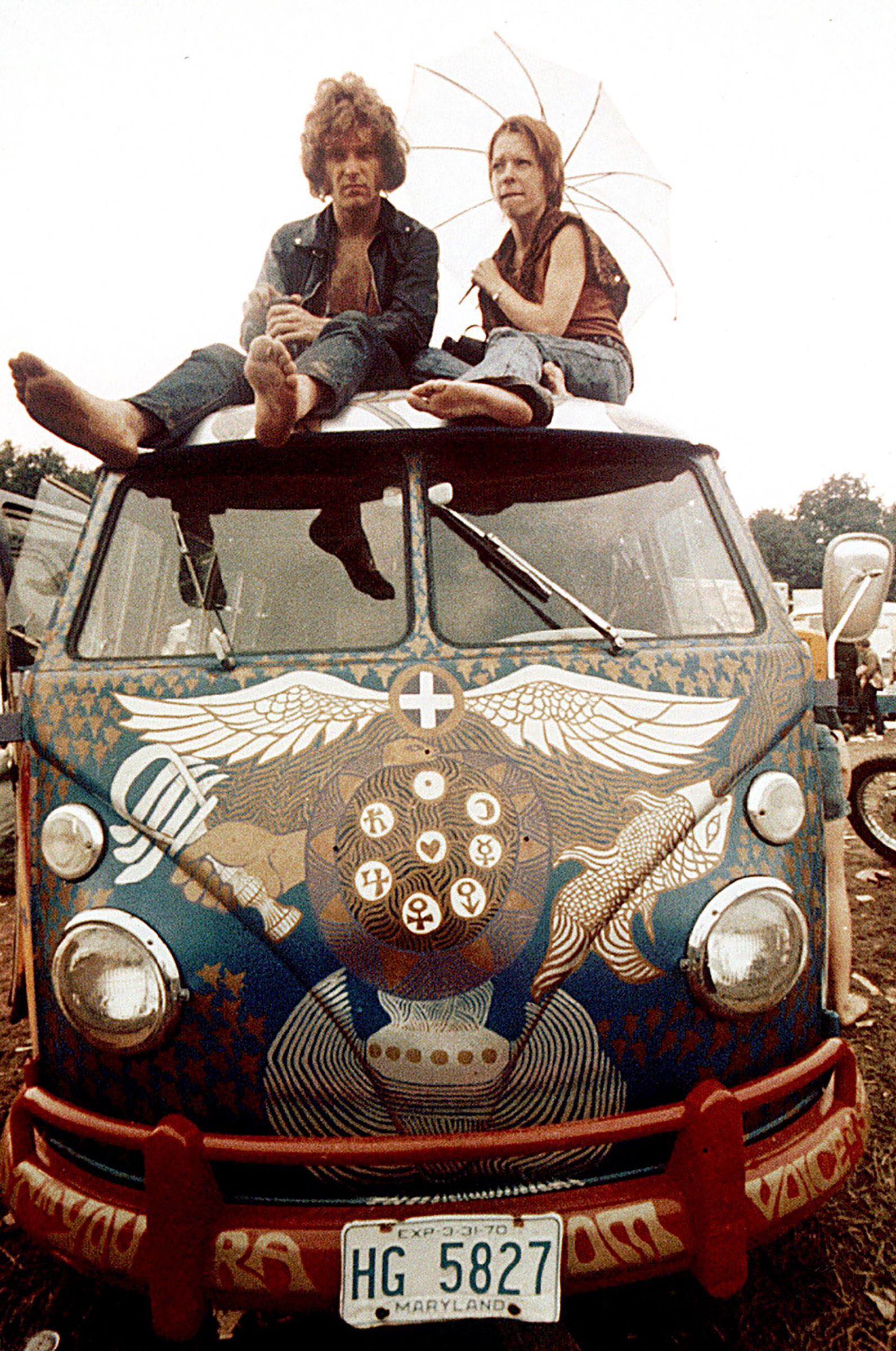 Concert-goers sit on the roof of a Volkswagen bus at the Woodstock Music and Arts Fair at Bethel, N.Y., in mid-August, 1969.