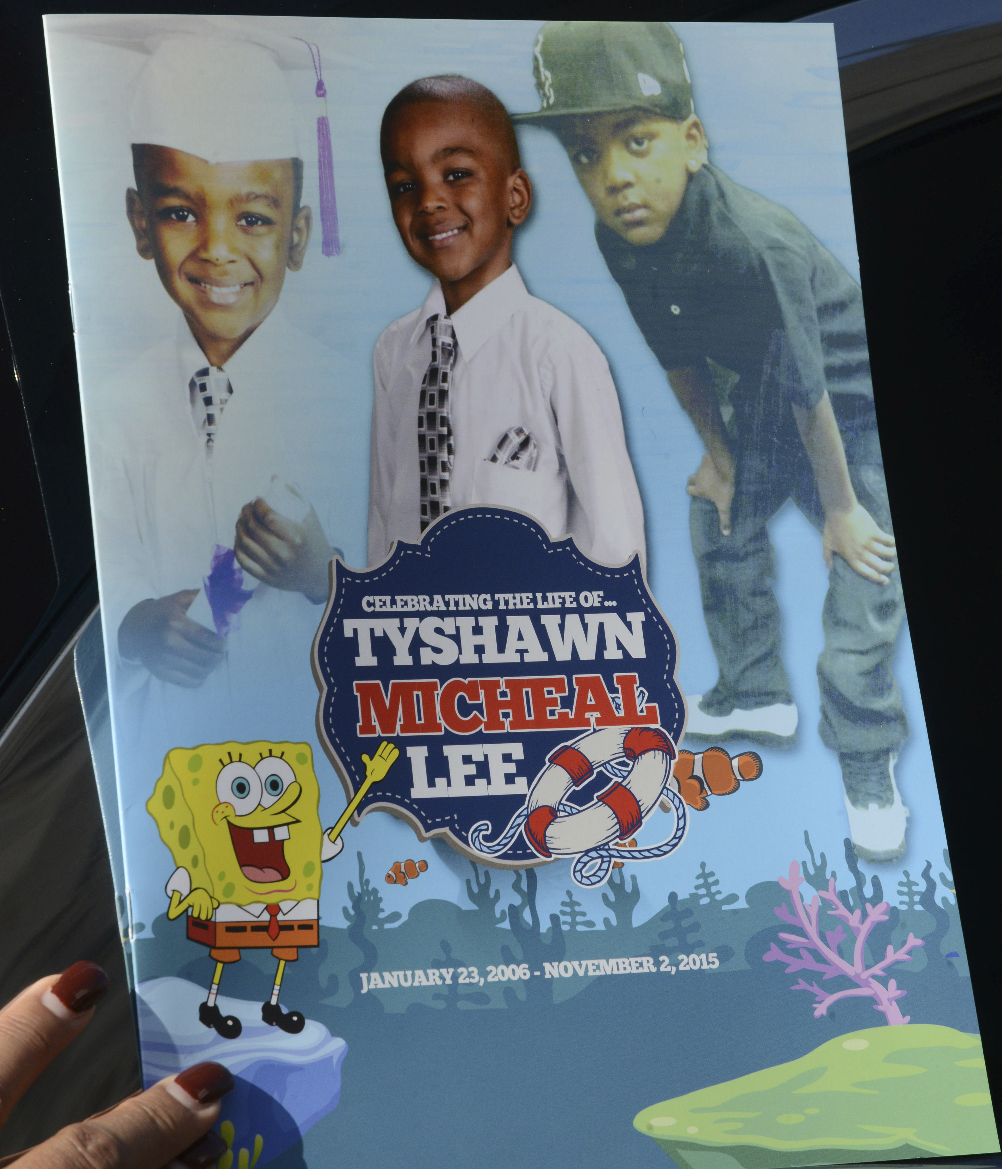 In this Tuesday, Nov. 10, 2015, file photo, a mourner holds the program for the funeral of 9-year-old Tyshawn Lee at St. Sabina Church in Chicago.