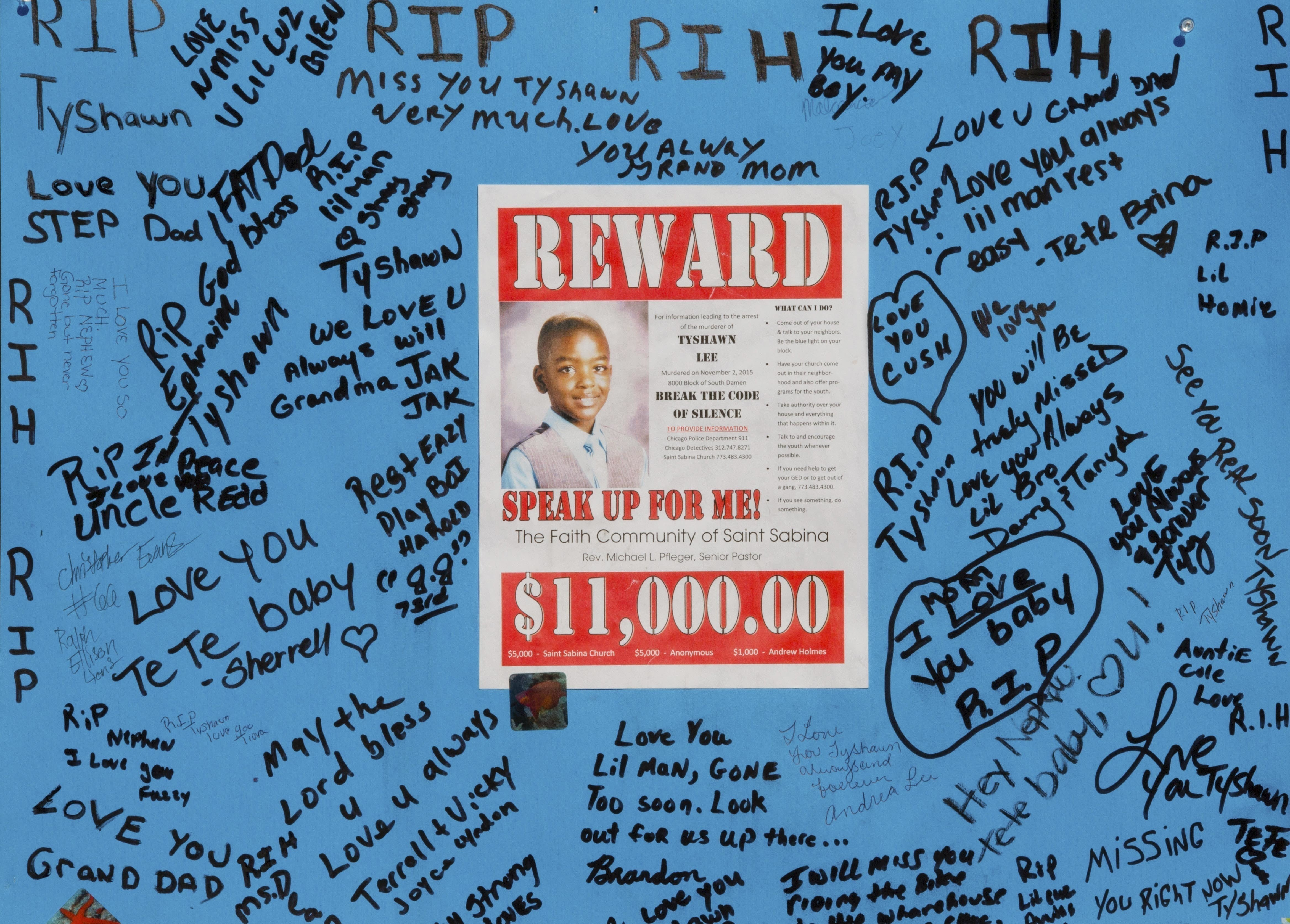 In this Nov. 4, 2015, file photo, a reward sign and messages hang near the site where Tyshawn Lee was fatally shot in Chicago.