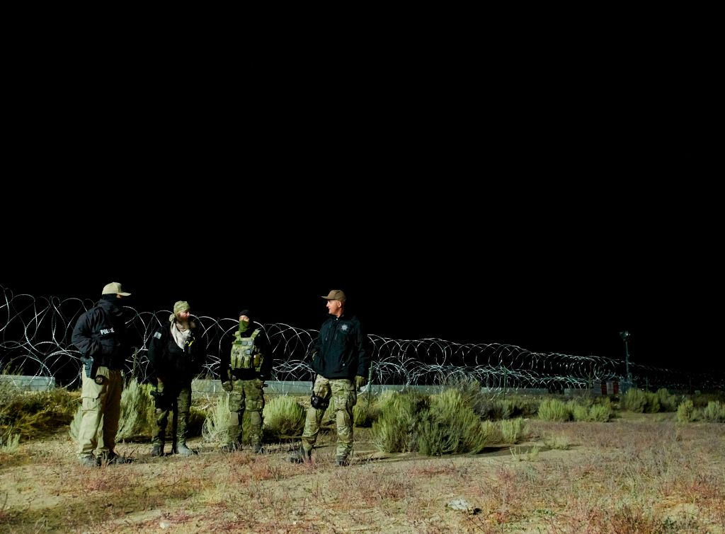 Members of law enforcement stand near barb wire, as people gathered to  storm  Area 51, at an entrance to the military facility near Rachel, Nevada on September 20, 2019. (Photo by Bridget BENNETT / AFP)        (Photo credit should read BRIDGET BENNETT/AFP/Getty Images)
