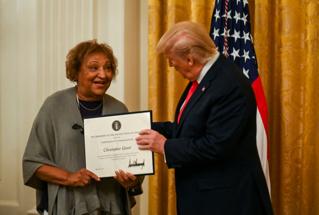 In the East Room of the White House, Donald Trump presents a Certificate of Commendation to Mimi Grant on behalf of her son, Christopher.