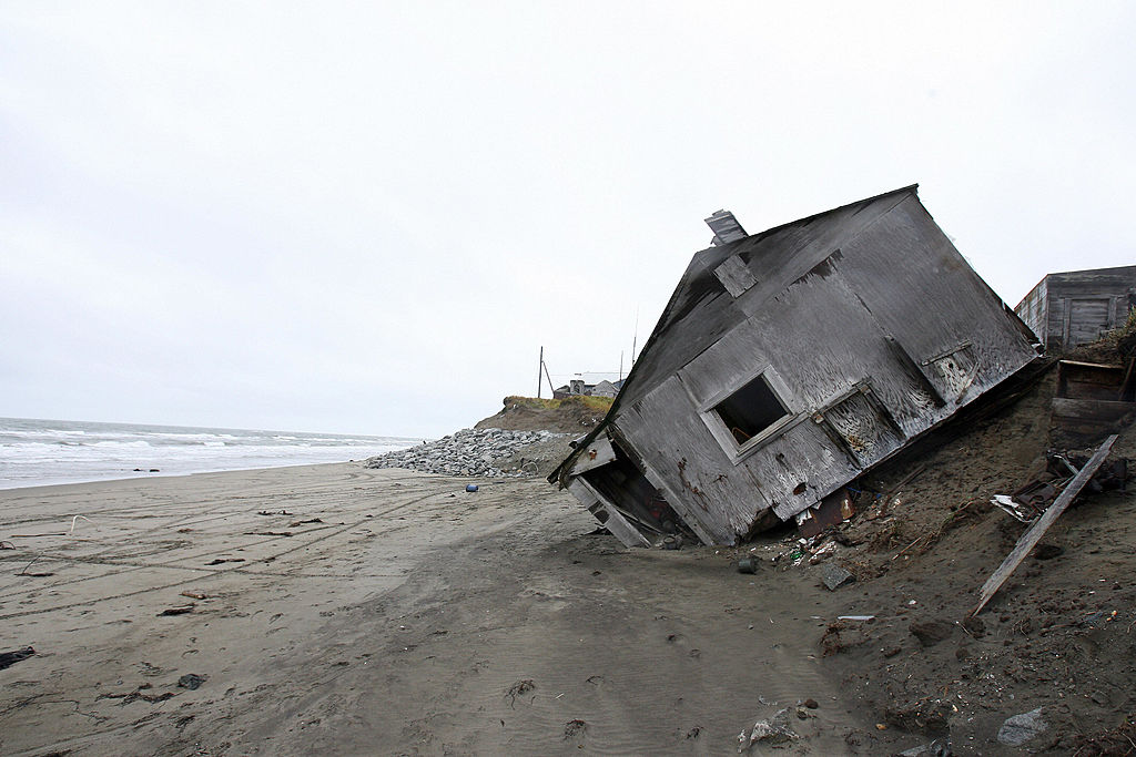 A home destroyed by beach erosion lies on its side on Sept. 27 2006 in the the Alaskan village of Shishmaref, which is facing evacuation because of global warming. Temperatures that have risen 15F (4.4C) over the last 30 years are causing a reduction in sea ice, thawing of permafrost along the coast, making the shoreline vulnerable to erosion.