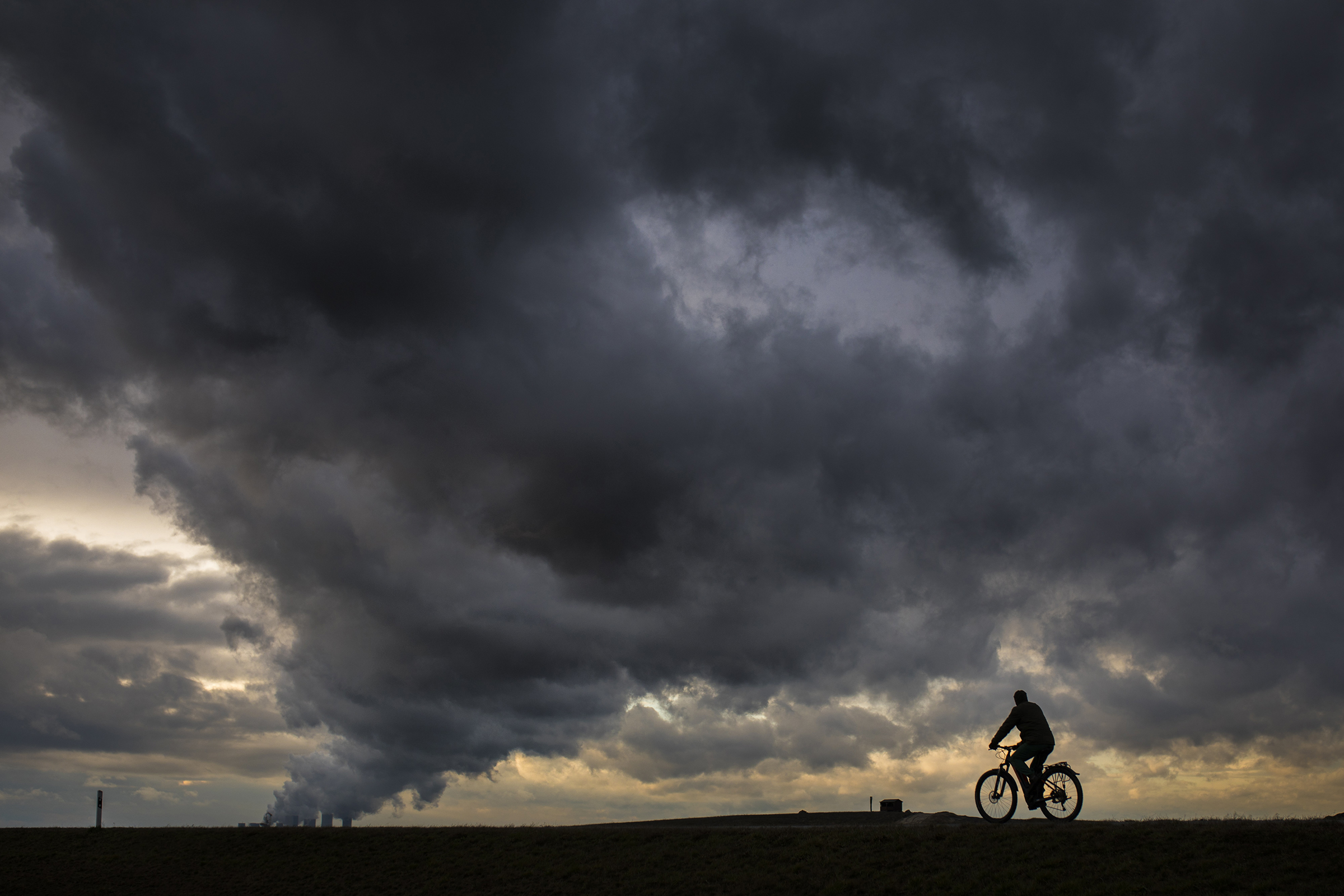 A cyclist is pictured in front of a lignite-fired power station of on March 11, 2019 in Germany.