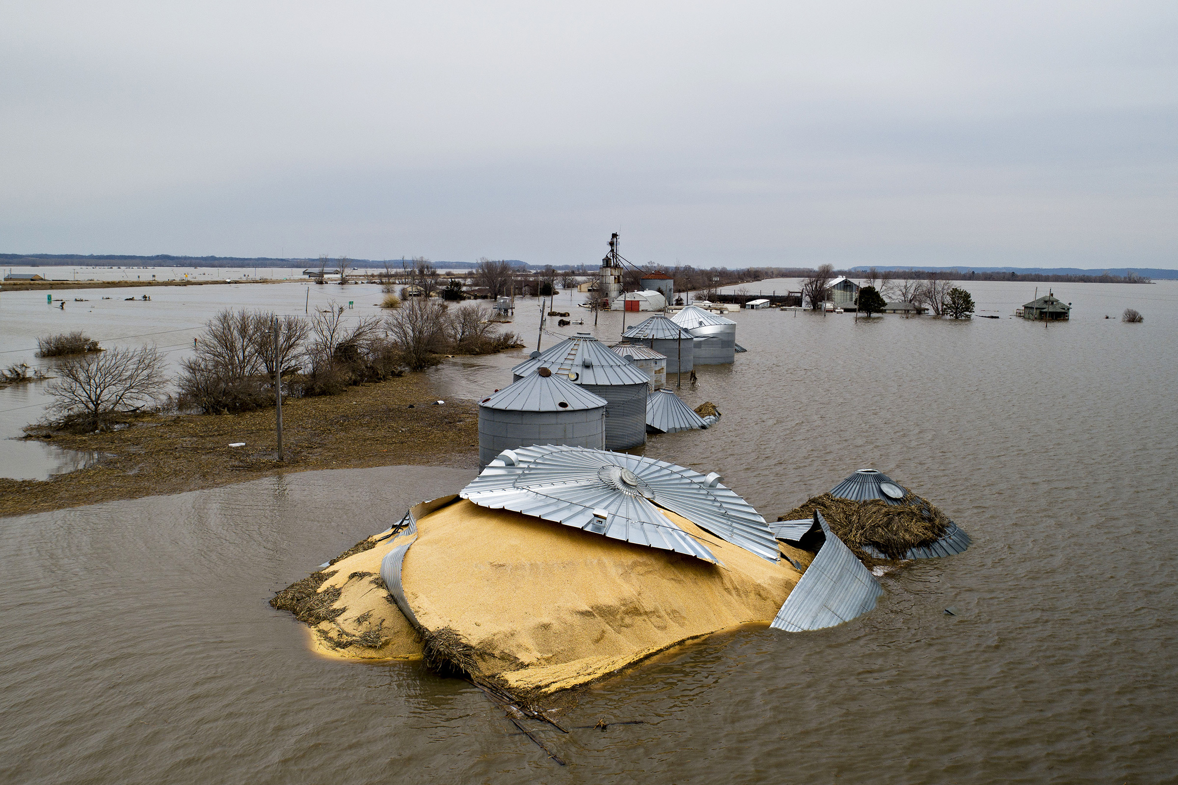 Floodwaters surround corn sitting under a collapsed grain bin in this aerial photograph over Thurman, Iowa, U.S., on Saturday, March 23, 2019.