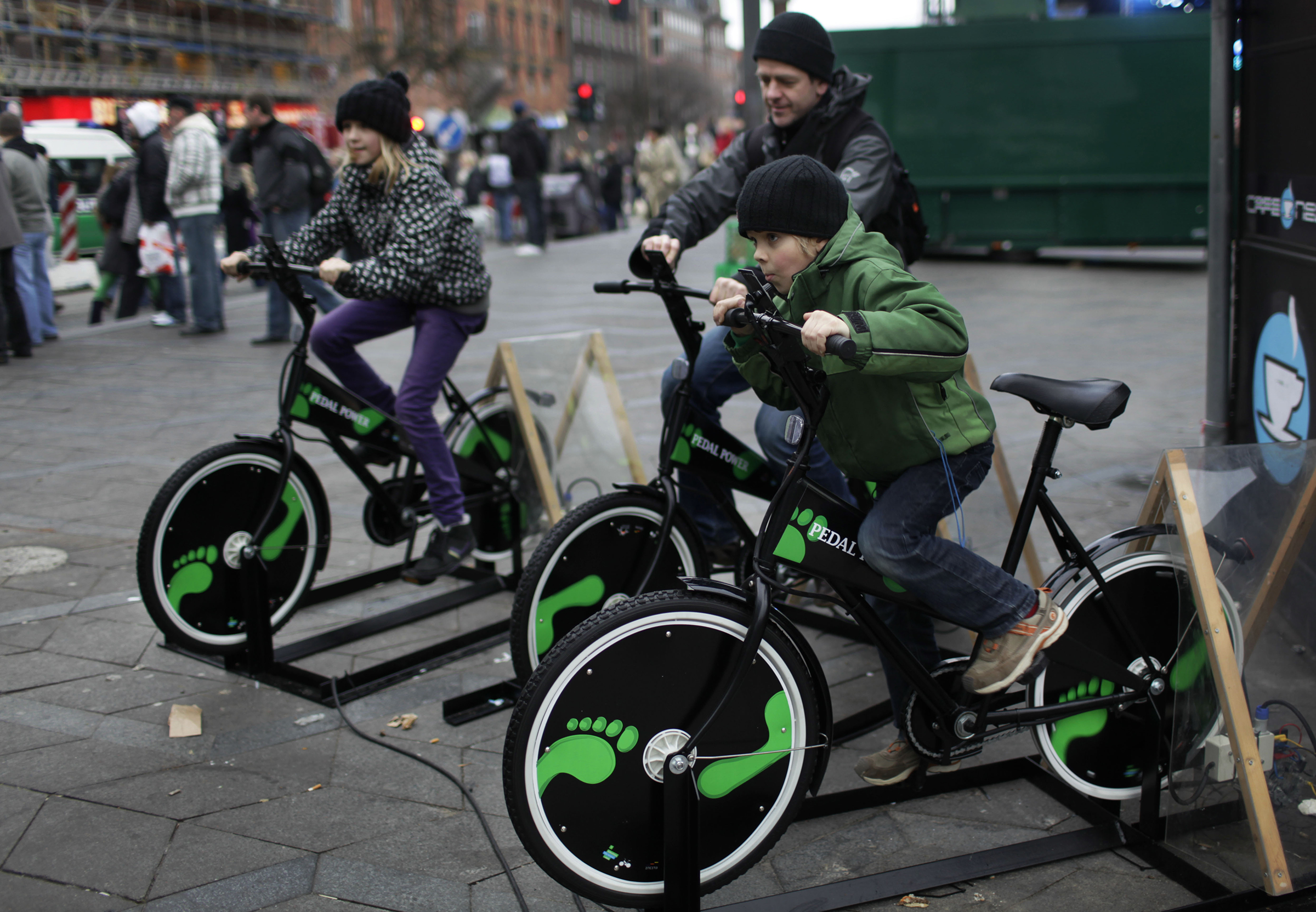 Danish people try out bicycles being set up to produce electricity in the center of Copenhagen, Denmark.