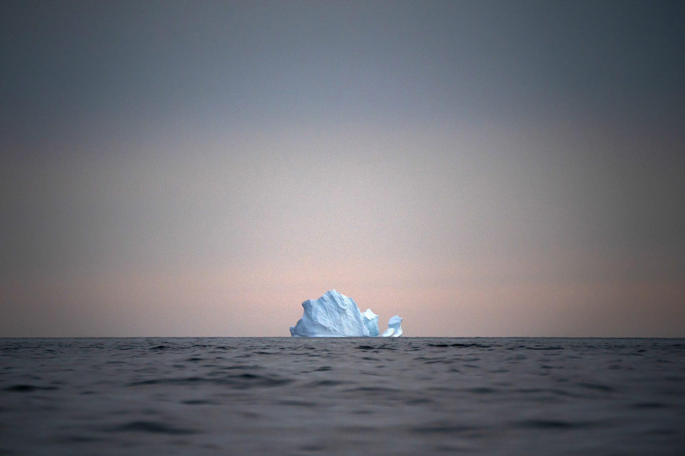 In this Aug. 15, 2019, photo, a large Iceberg floats away as the sun sets near Kulusuk, Greenland.